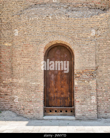 Grunge wooden aged vaulted door on exterior stone bricks wall of Amr Ibn Al-As, Medieval Cairo, Egypt - Stock Image