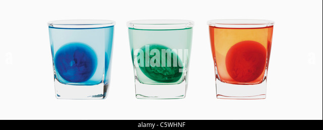 Three coloured eggs in three glasses on white background, close up - Stock Image