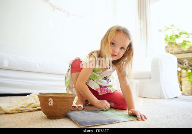 Portrait of innocent little girl painting a picture. Schoolgirl sitting on the floor coloring looking at camera - Stock Image