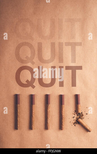 Quit smoking concept, flat lay arranged cigarettes with broken one at the end as final decision to quit is made - Stock Image