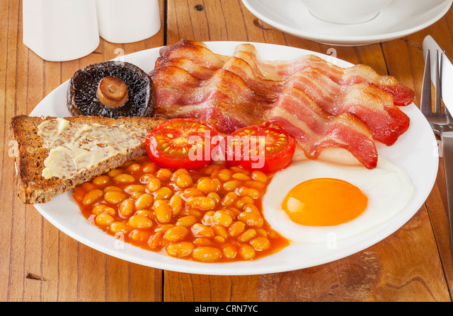 Full English breakfast on an old pine kitchen table. - Stock Image