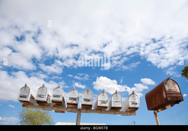 A row of mailboxes viewed from a low angle against the sky - Stock Image