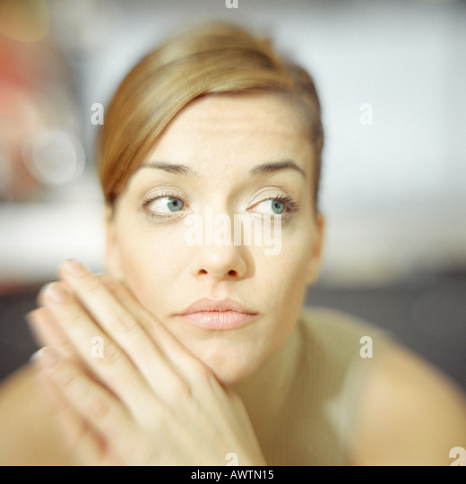Young woman, hands to chin, looking to the side, portrait - Stock Image