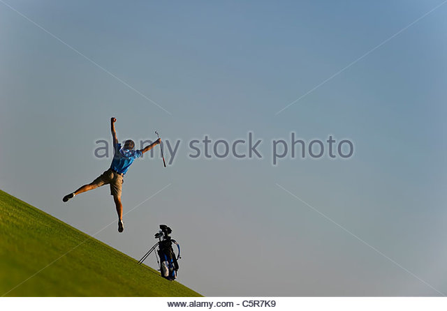 A golfer leaps into the air in celebration. - Stock-Bilder