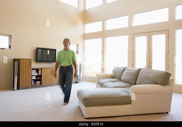 Man walking through living room - Stock Image