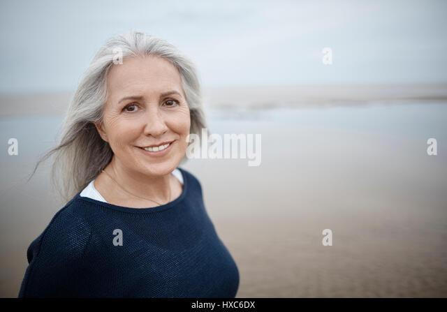 Portrait smiling senior woman on beach - Stock Image
