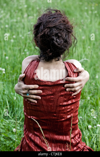 a woman sitting on a lawn, hugging herself - Stock Image