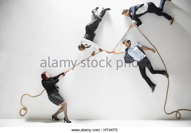Businesswoman pulling businessmen floating on rope against white background - Stock-Bilder