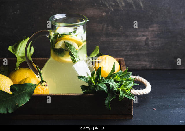 Homemade mint lemonade served with fresh lemons and ice over wooden background, top view, copy space - Stock Image