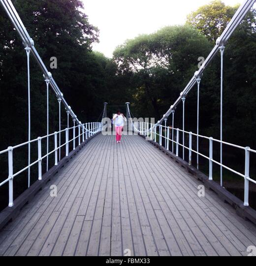 Woman Standing On Bridge In Forest - Stock Image