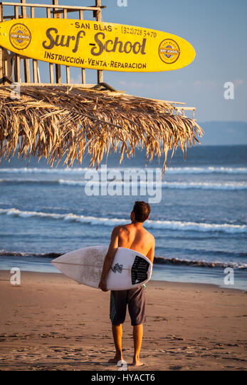 A surfer arrives at the San Blas surf school on the beach of San Blas, Nayarit, Mexico. - Stock Image