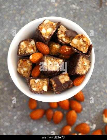 Chocolate candy bars cut into pieces mixed with whole almonds in white porcelain bowl - Stock Image