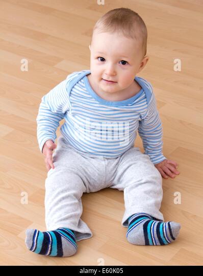 beautiful laughing baby boy sitting - Stock Image