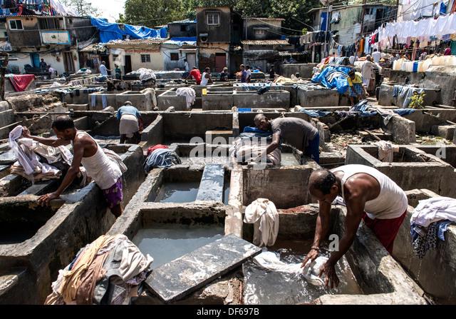 Indian men washing clothes at Mahalaxmi Dhobi Ghat or laundromat Mumbai India - Stock Image