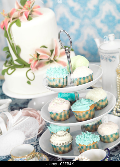 Food still life photo of cupcakes, china and a cake on a table - Stock Image