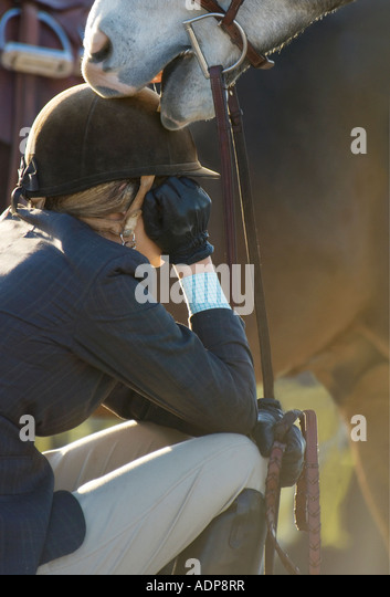A tender moment during lull in action between teen girl and her horse at show jumping event - Stock Image