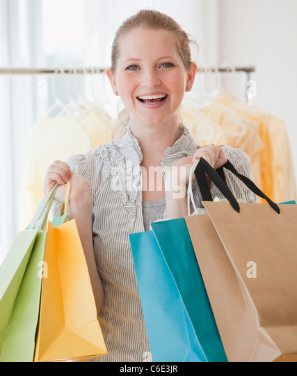 USA, New Jersey, Jersey City, Young woman with shopping bags - Stock Image