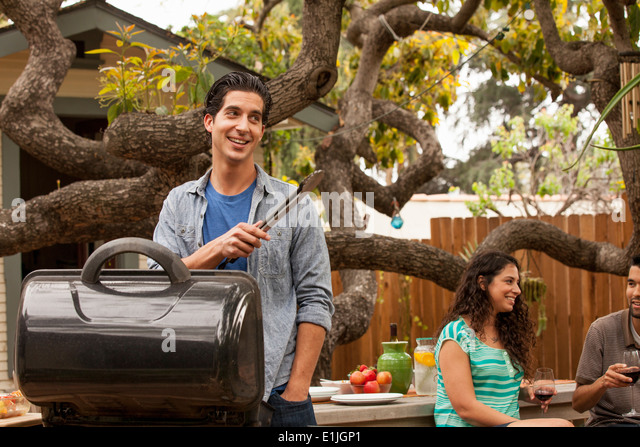 Man cooking on barbecue, friends in background - Stock Image