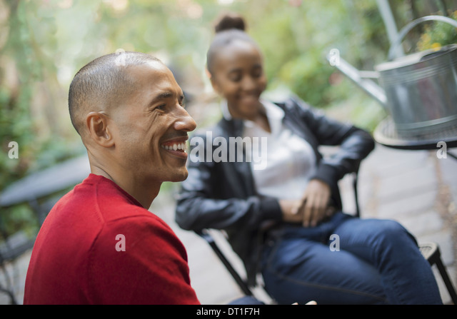Scenes from urban life in New York City A man and a teenage girl sitting outdoors Laughing - Stock Image