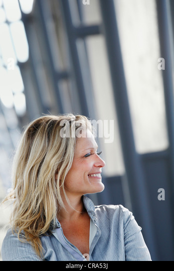 Smiling businesswoman standing outdoors - Stock Image