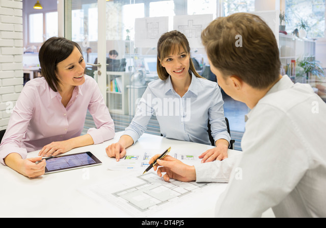 Cheerful Architect team working in meeting room - Stock Image