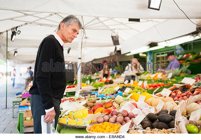 Senior man browsing fruit and vegetables on market stall - Stock Image