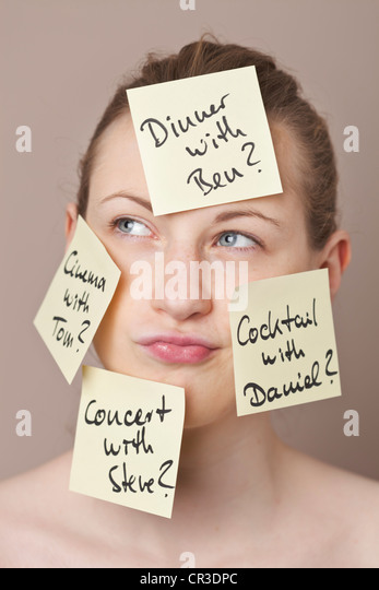 Post-It notes written in German with date options, sticking to the face of an indecisive young woman - Stock Image