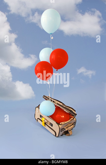 balloons rise from open suitcase - Stock Image