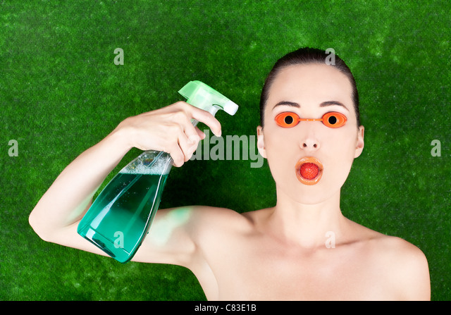 Closeup of a woman wearing tanning bed glasses with strawberry in mouth and spray bottle in hand against green - Stock Image