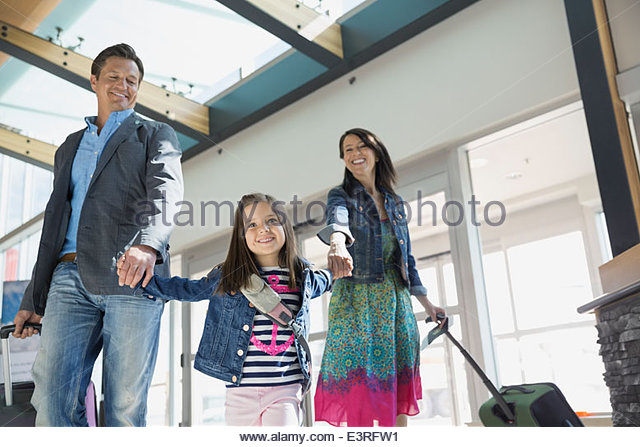 Daughter leading parents in airport - Stock Image