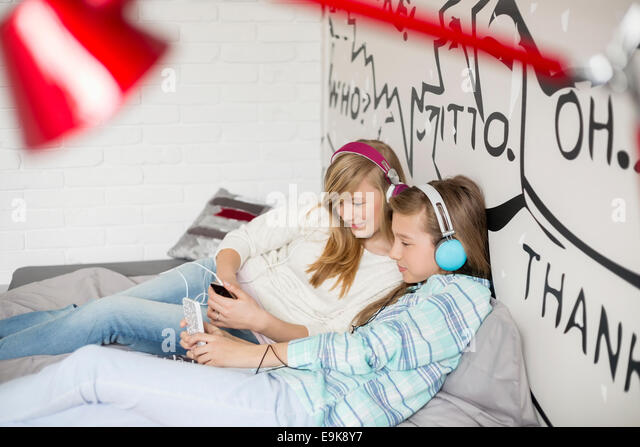 Relaxed sisters listening to music at home - Stock-Bilder