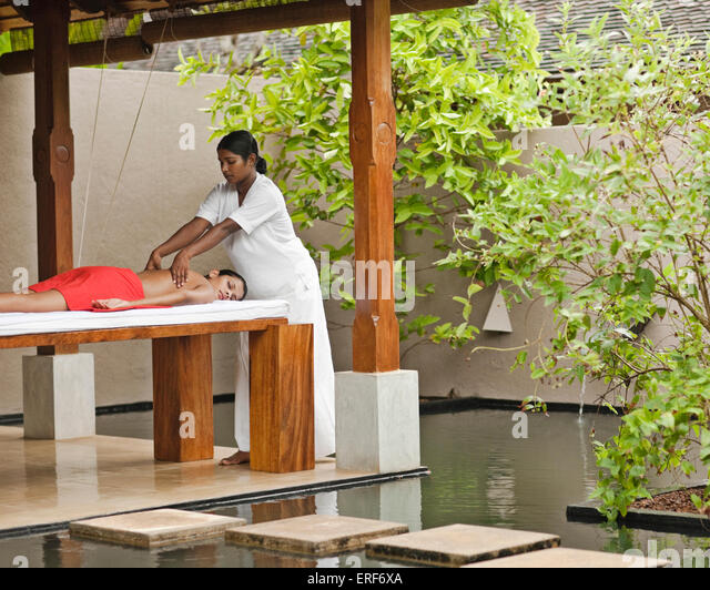 A woman receives a Deep Tissue Massage at the Sahana Spa, Saman Villas, Aturuwella, Bentota, Sri Lanka. This massage - Stock Image