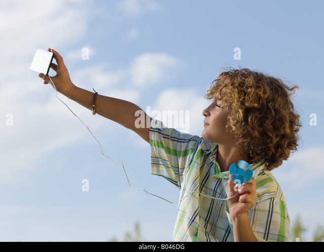 Boy using a small solar panel - Stock Image
