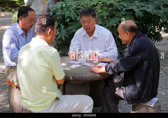 China Shanghai Huangpu District Nanjing Road People's Park Asian man playing cards gambling watching card game - Stock Image