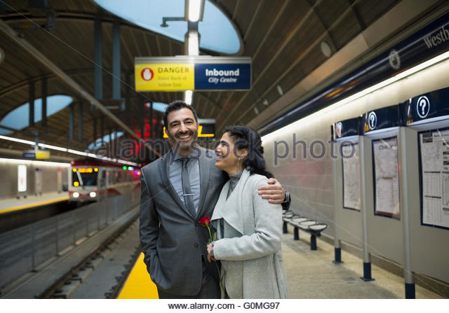 Smiling couple hugging on subway station platform - Stock Image
