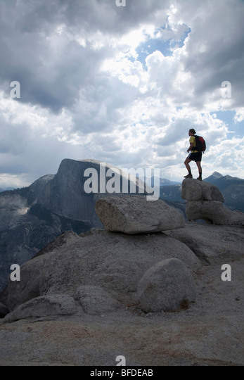A female hiker on granite boulders on the North Dome at Yosemite National Park, with Half Dome in the background. - Stock Image
