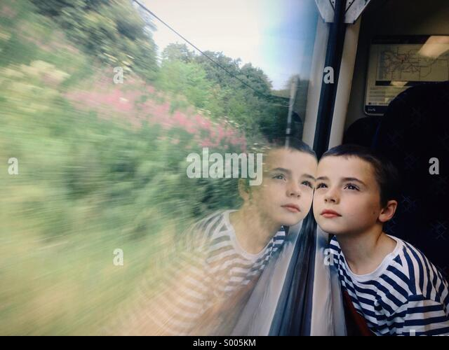 Young boy gazing out of train window - Stock Image