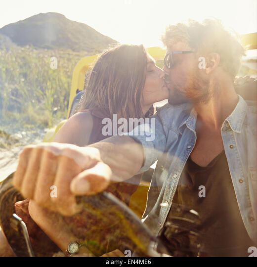 Young couple kissing in the car. Couple in love on road trip having fun. - Stock Image
