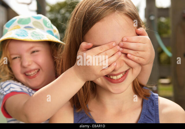 Girl with hands over her sisters eyes in garden - Stock Image