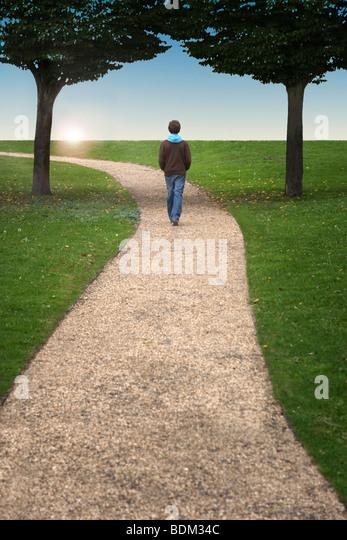 A boy walking along a winding path between two trees towards a setting sun - Stock Image