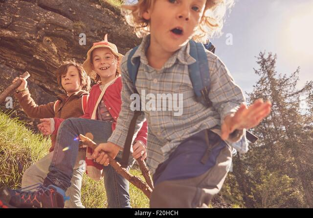 Three children exploring forest - Stock Image
