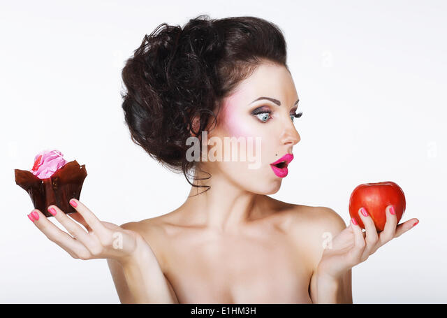 Surprised Funny Woman Decides between Apple and Cake - Stock Image