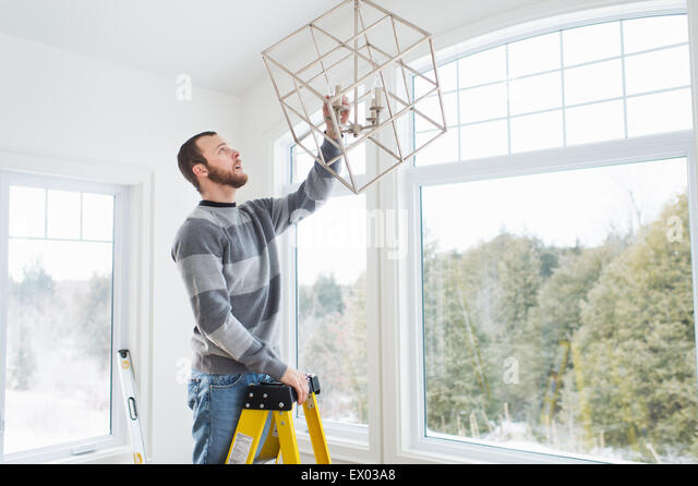 Young man installing ceiling light - Stock-Bilder