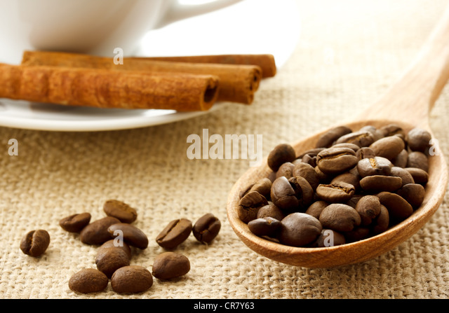 Coffee Beans in a Wooden Spoon with Cinnamon Sticks and Coffee Mug - Stock Image