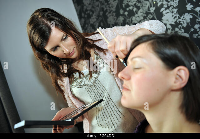 A Makeup Artist applies make-up for a young woman. - Stock Image