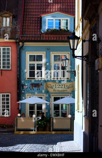 Facades of old houses with flowers on windows and street cafes of Riga on a sunny day in spring - Stock Image