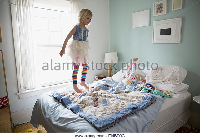 Girl in tutu jumping on bed - Stock Image