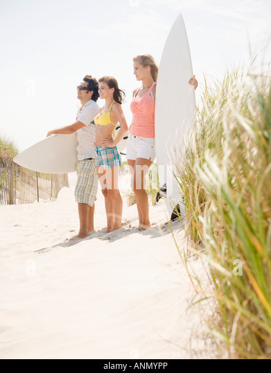 Friends holding surfboards at beach - Stock Image