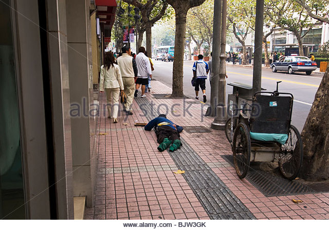 Beggar lying on Shanghai city street - Stock Image