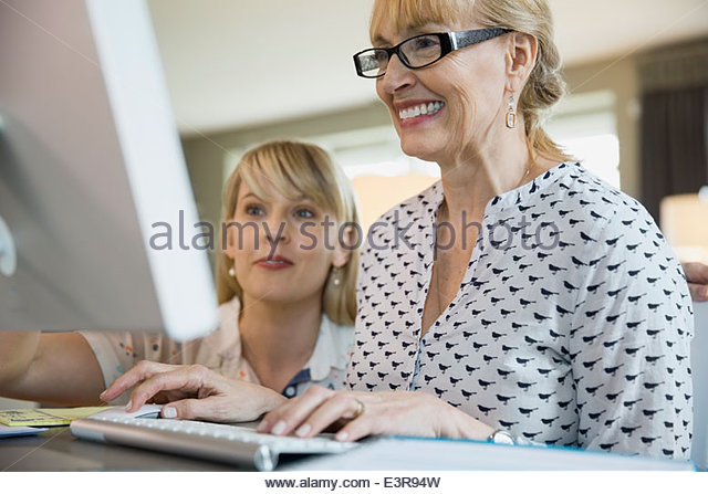 Mother and daughter using computer - Stock Image